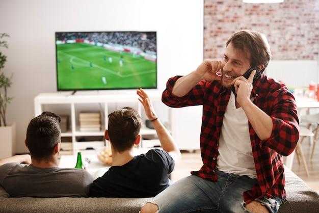 Man praten via de telefoon tijdens voetbalwedstrijd