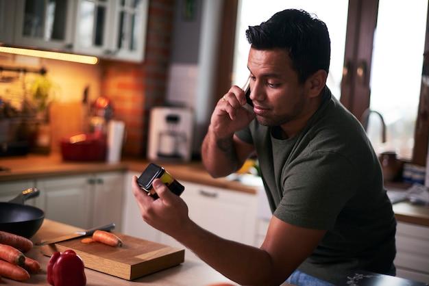 Man praten via mobiele telefoon tijdens het koken