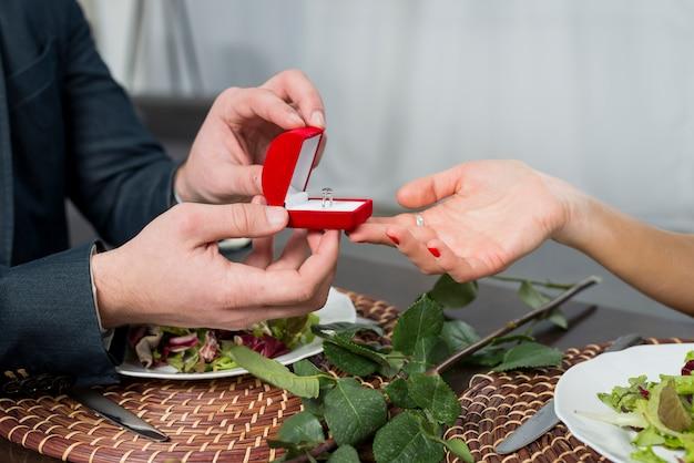 Man presenteert geschenkdoos met ring aan vrouw aan tafel met gerechten en bloei