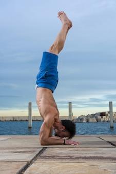 Man presterende geavanceerde yoga-oefeningen en stretching.