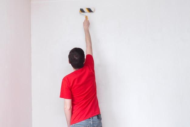 Man primeert de muur met een roller reparatie van het interieur met kopieerruimte
