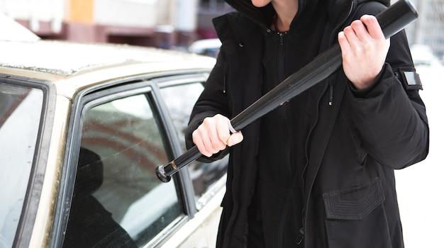 Man probeert het raam van een auto te breken met een honkbalknuppel