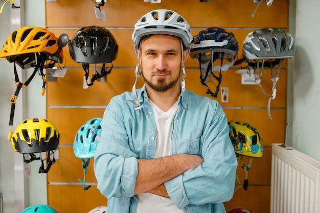 Man probeert op fietshelm, winkelen in sportwinkel.
