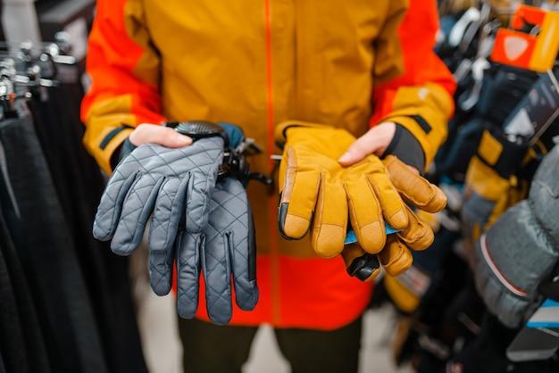 Man probeert op handschoenen voor skiën of snowboarden
