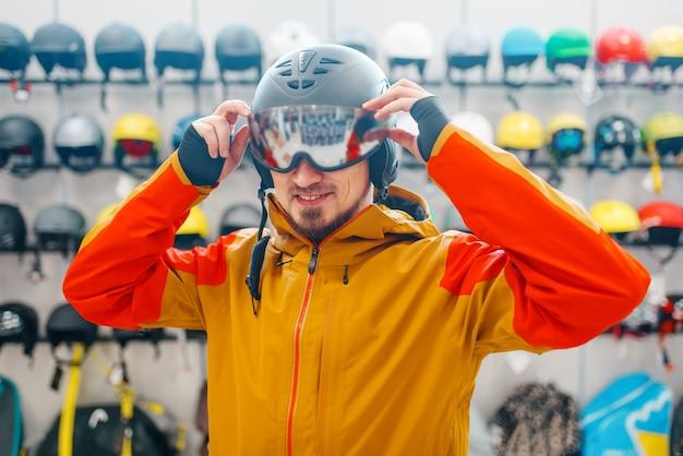 Man probeert op helm voor skiën of snowboarden