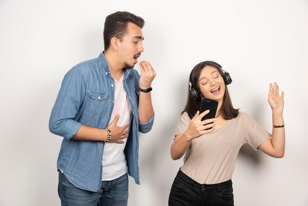 Man probeert te praten met vrouw die naar muziek luistert.