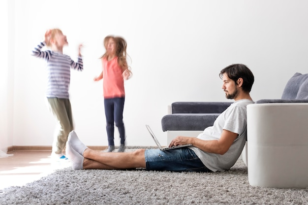 Man probeert thuis op laptop te werken terwijl haar kinderen rondrennen