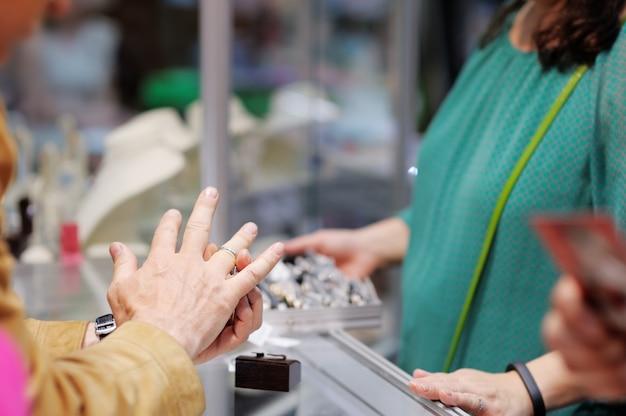 Man probeert trouwringen op een juwelier, focus op ring