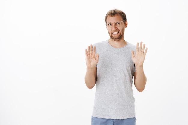 Man probeert voorstel te weigeren is niet in de stemming, handpalmen opheffen in afwijzingsgebaar, tanden op elkaar klemmen en een droevige uitdrukking geven, niet bereid ergens heen te gaan aanbod afwijzen