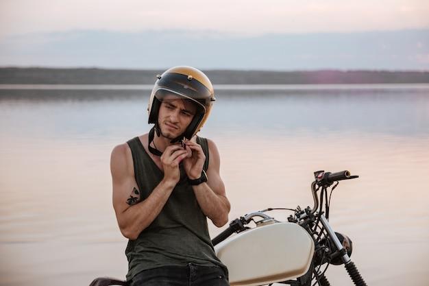 Man probeert zijn helm af te zetten terwijl hij op zijn motor zit