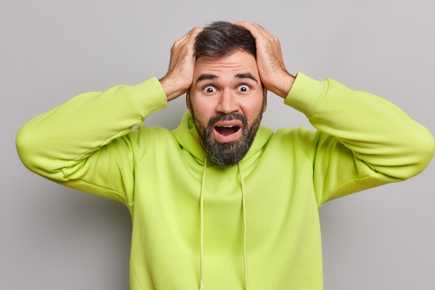 Man raakt hoofd aan met schok heeft coronavirus paniek kijkt verbaasd weet niet wat te doen in moeilijke situatie gekleed in hoodie poseert op grijs