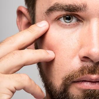 Man raakt zijn gezicht close-up aan