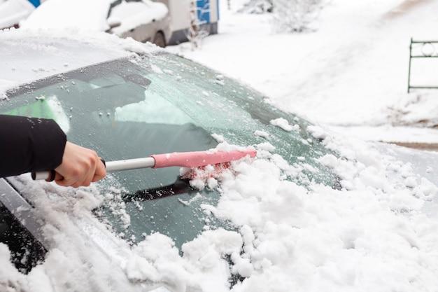 Man reinigt de auto van sneeuw met een borstel