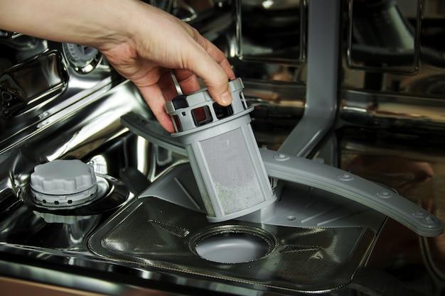 Man reinigt het filter in de vaatwasser. onderhoud van huishoudelijke apparaten.