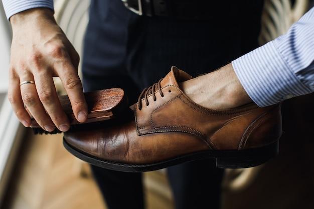 Man reinigt schoenen met een borstel van vuil
