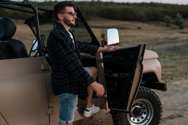 Man reist alleen met de auto terwijl hij een zonnebril draagt