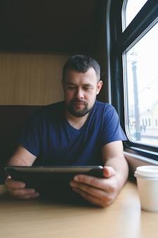 Man reist met de trein bij het raam zit met een tablet