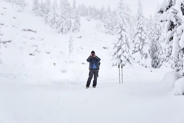 Man reiziger fotografeert de natuur in een bergachtig winterbosgebied
