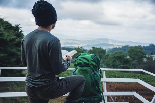 Man reiziger leest boek reist natuur op de berg in de frisse lucht in het noorden, chiang mai in thailand.