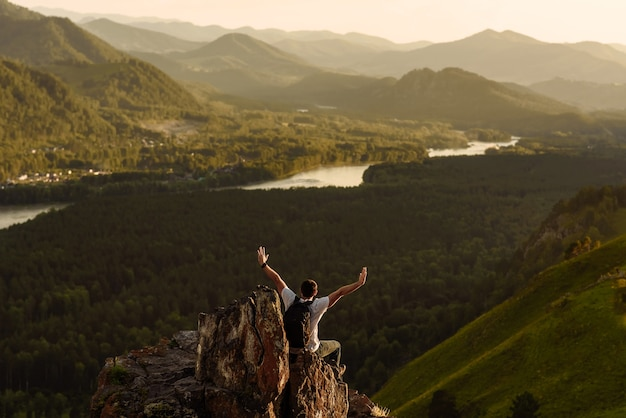Man reiziger met rugzak met opgeheven armen genieten van het uitzicht op de vallei