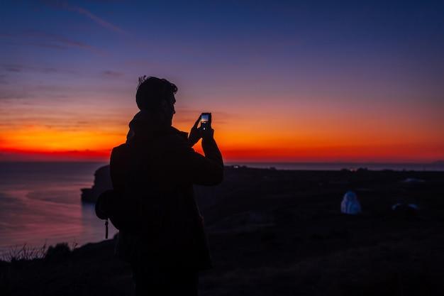 Man reiziger silhouet wandelen bij zonsondergang op santorini eiland. toerist die foto van nachtlandschap op smartphone nemen