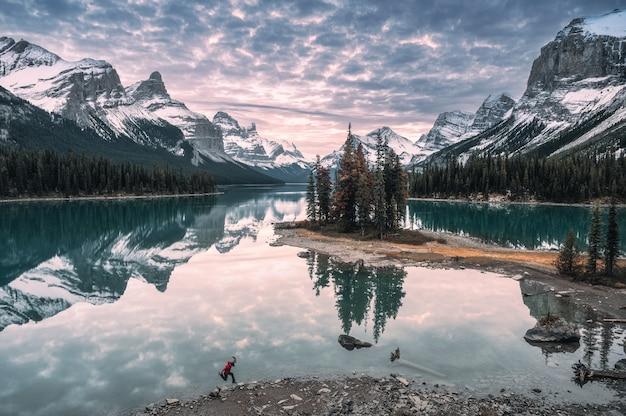 Man reiziger springen op de oever van het meer in spirit island op maligne lake in jasper national park, canada