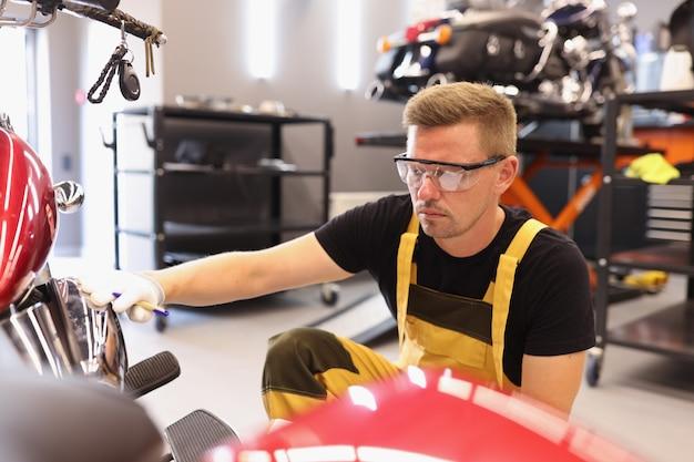 Man reparateur in bril oppakken van verf naar motorfiets in auto reparatiewerkplaats reparatie en