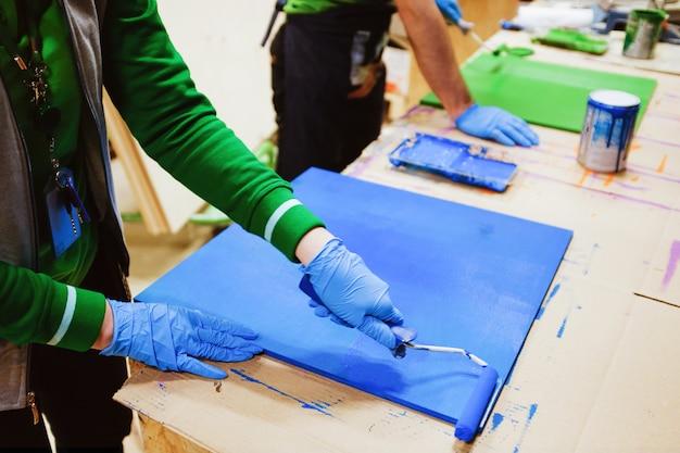 Man, reparateur, timmerman, ingehuurde werknemer schildert het bord. herenhanden in rubberen handschoenen rollen de verf uit met een roller op een houten plank. het thema van thuis- en professionele reparatie, bouw.