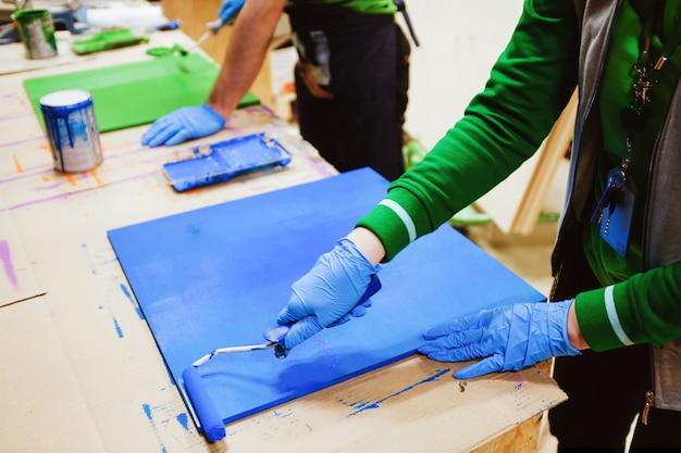 Man, reparateur, timmerman, ingehuurde werknemer schildert het bord. thuis- en professionele reparatie, bouw.