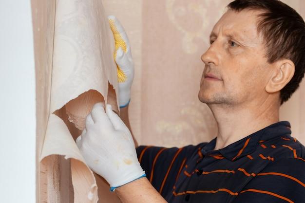 Man, reparateur verwijdert oud behang van de muur, vervangt behang