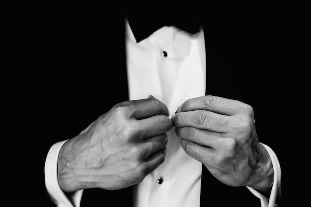 Man repareert knoppen op zijn witte shirt
