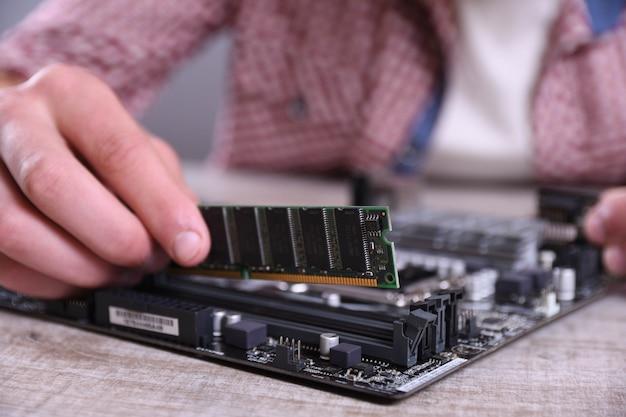 Man repareren van kapotte computer, videokaart, ram geheugen, koeler, processor, harde schijf. jonge reparateur werken met schroevendraaier in servicecentrum. tiener