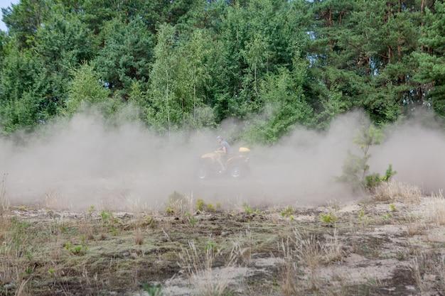Man rijden op een gele quad atv alle terreinvoertuig op een zandig bos