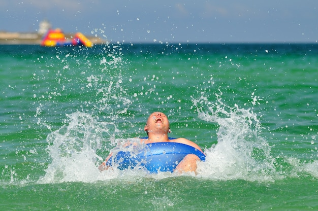 Man rijden op zwemmen cirkel in zee en lachend op zonnige zomerdag. geluk, vakanties en vrijheidsconcept
