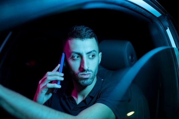 Man rijdende auto 's nachts met mobiel