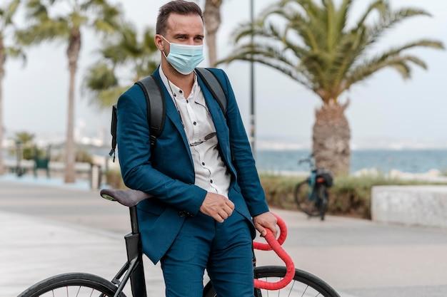 Man rijdt op een fiets terwijl hij een medisch masker draagt om te werken