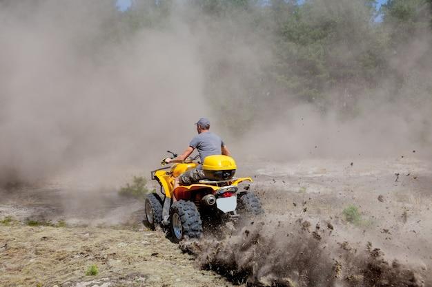 Man rijdt op een gele quad atv terreinwagen op een zanderig bos