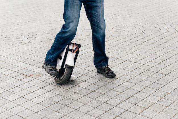 Man rijdt snel op elektrische eenwieler op straat.