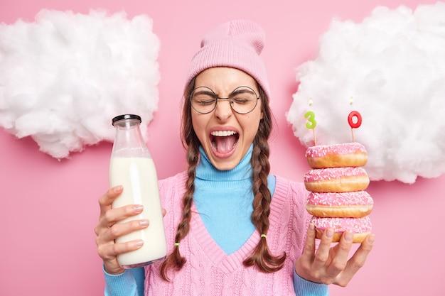 Man roept luid viert verjaardag alleen eet lekkere donuts met melk houdt mond wijd open draagt hoed vest en coltrui ronde bril staat binnen