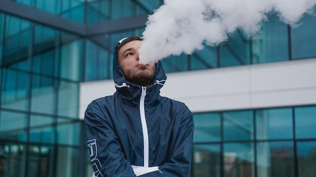 Man roken elektronische sigaret damp. elektronische sigaret roken tegen de achtergrond van een glazen gebouw