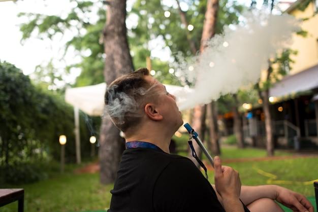 Man roken shesha, waterpijp waterpijpen in de natuur op een warme zonnige dag. oosterse waterpijp roken, actieve rec