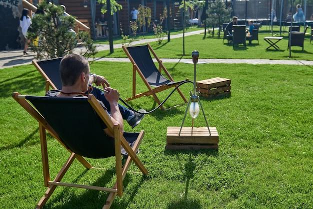 Man roken shesha, waterpijp waterpijpen in de natuur op een warme zonnige dag. oosterse waterpijp roken, actieve recreatie in de frisse lucht. ligstoelen op geen gras. de plek voor vrije tijd,