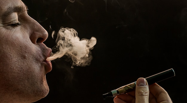 Man roken sigaret op zwarte achtergrond, knappe jonge man roken sigaret, mystery man met sigaar en rook geïsoleerd op zwarte achtergrond