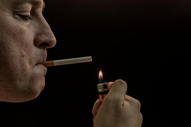 Man rokende sigaret op zwarte achtergrond. mysterie man met sigaar en rook geïsoleerd op zwarte achtergrond. donkere en dwaze schot van een jonge man die op een zwarte achtergrond rookt