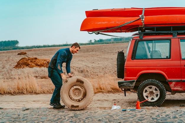 Man rolt een nieuw vervangwiel naar 4x4 off-road truck
