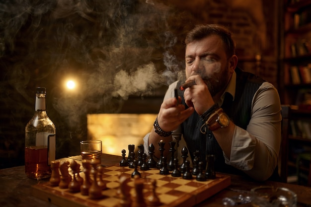 Man rookt een sigaar, drinkt alcoholische drank en speelt schaak, boekenplank en vintage kantoorinterieur op achtergrond