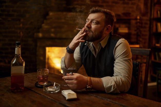 Man rookt sigaret en drinkt alcoholische drank, boekenplank en rijk kantoorinterieur. tabaksrookcultuur, specifieke smaak
