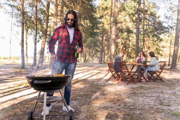 Man roostert maïs op de barbecue terwijl vrienden aan tafel praten