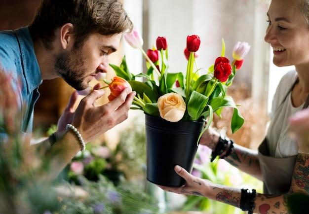 Man ruikende verse bloemen in een pot