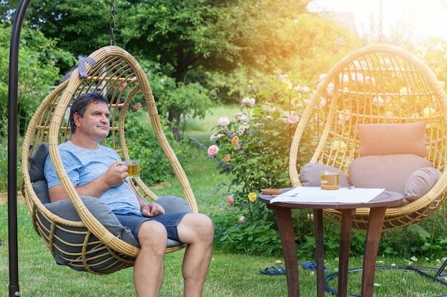 Man rust in rotan cocon rieten stoel met kopje thee in de buurt van bloeiende rozen in de achtertuin in de zomer, zonnige dag